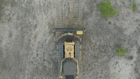Tracked bulldozer driving on a sandy road