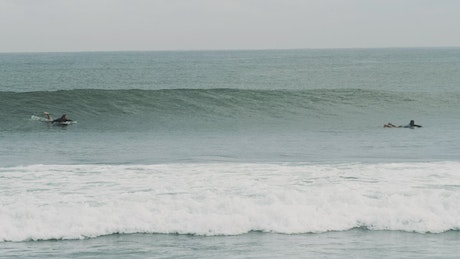 Tracking shot of a person surfing waves