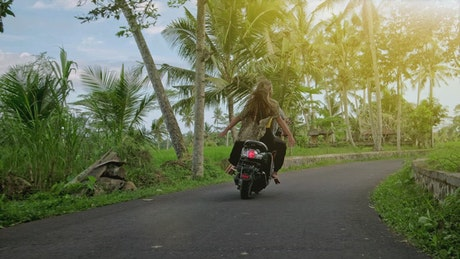 Tracking shot of a wanderlust couple riding a motorcycle