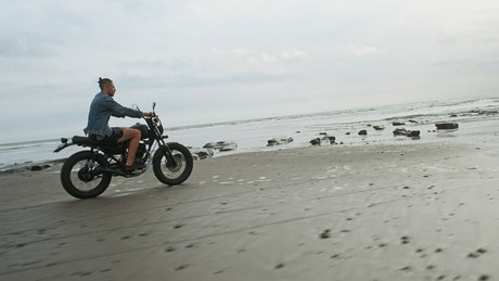 Tracking shot of a wanderlust riding a motorbike at the beach