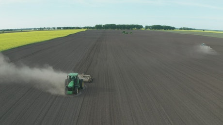 Tractor driving along a dusty field