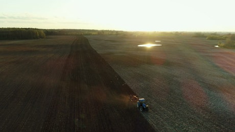 Tractor working in the field with sunbeams