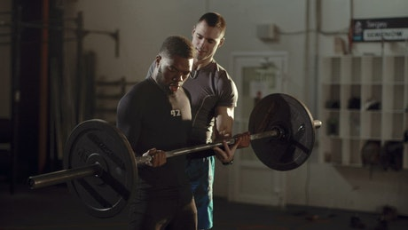 Trainer helping athlete with the barbell