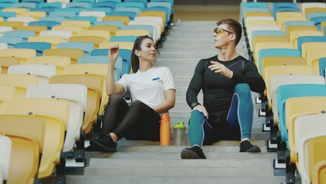 Trainer hi-fives winner after race sitting on stadium stairs