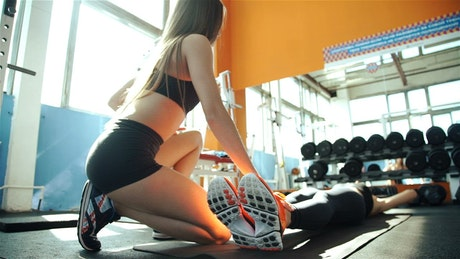 Trainer holds legs for woman doing sit ups in gym