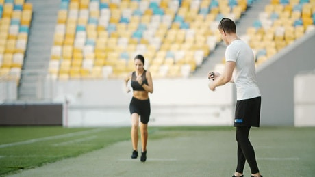 Trainer motivates athlete on running track