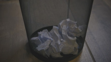 Trash basket of an office with paper balls