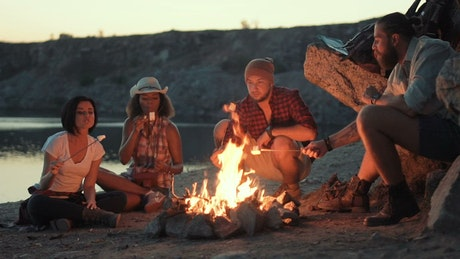 Travelers cooking marshmallows in the bonfire
