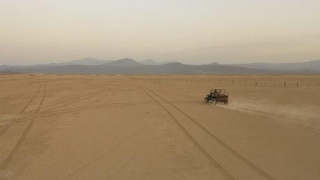 Traveling arid desert aboard a jeep, aerial shot
