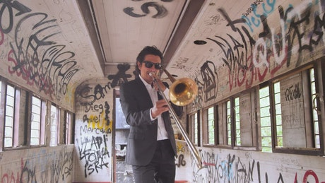 Trombone musician in a train car