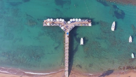 Tropical pier with umbrellas and boats