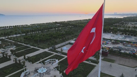 Turkey flag waving on top of a city, aerial shot