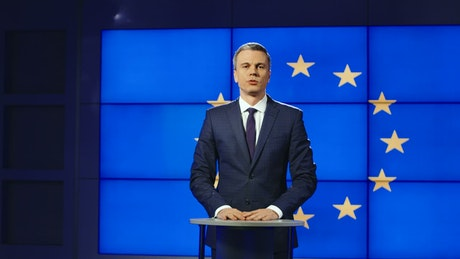 TV news presenter with Europe flag behind