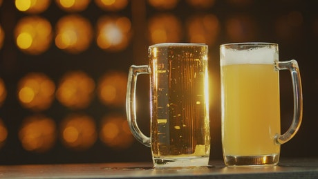 Two beers against an orange background