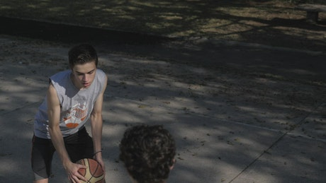 Two boys playing basketball one on one