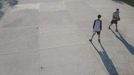 Two boys playing basketball outdoors