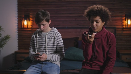 Two boys using their phones