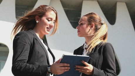 Two business women commenting on something on a tablet