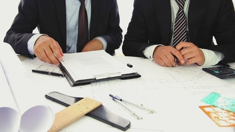 Two businessmen in suits reviewing some documents