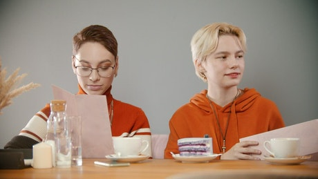 Two cheerful women ordering in a restaurant