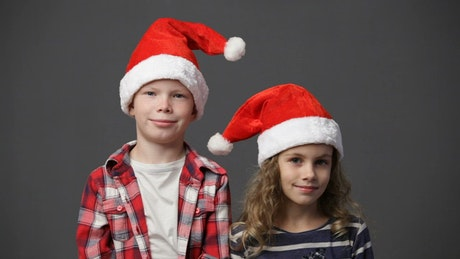 Two children in Christmas hats