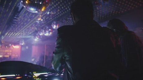 Two DJ's mixing music at a nightclub