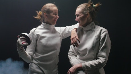 Two fencer friends talking after a duel