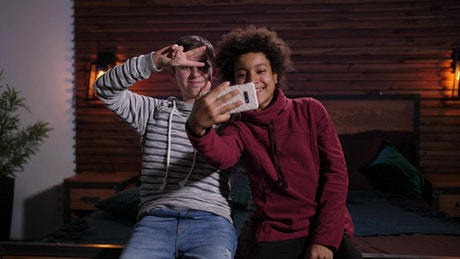 Two friends playing with a phone camera