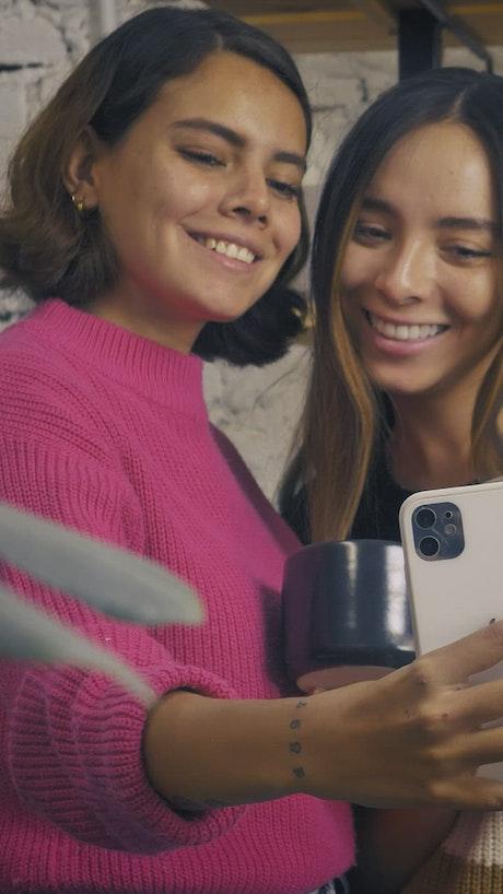 Two friends taking a selfie in a ceramic vase shop