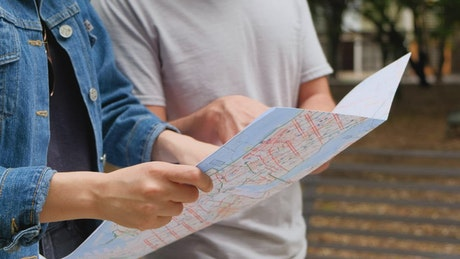 Two friends walking through a park while looking at a map