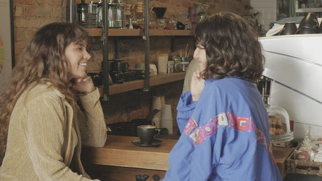 Two girls chatting at the counter of a coffee shop
