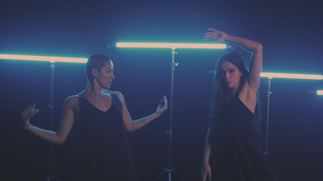 Two girls dancing with blue neon lights in the background