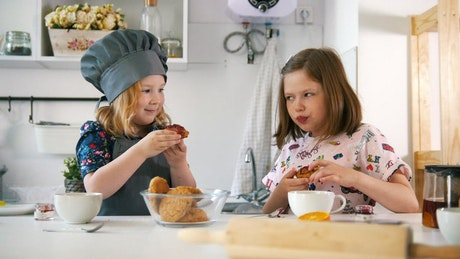 Two girls in a kitchen eating fresh cookies