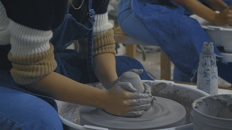 Two girls molding clay during a pottery class