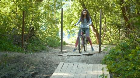 Two girls riding bikes in an adventure park