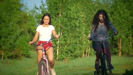 Two girls riding bikes in nature