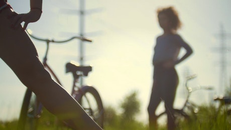 Two girls stretching during a bike ride