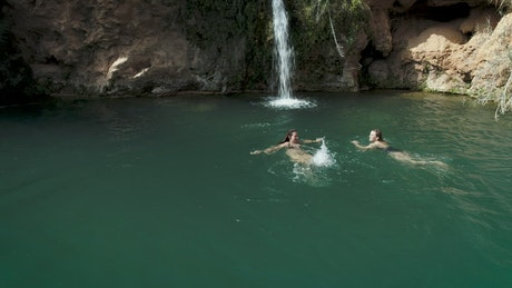 Two girls swimming in a pond with a waterfall