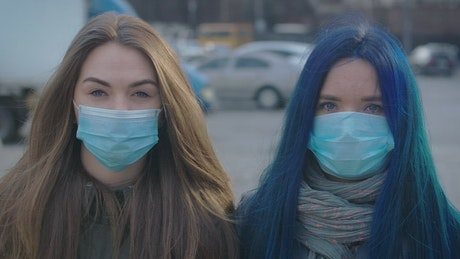 Two girls with masks on the street