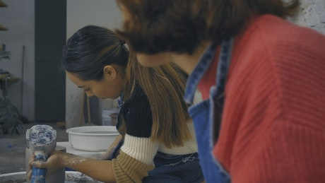 Two girls working with clay in a pottery workshop