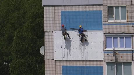 Two industrial climbers rebuilding a facade