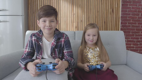 Two kids play console games and celebrate win