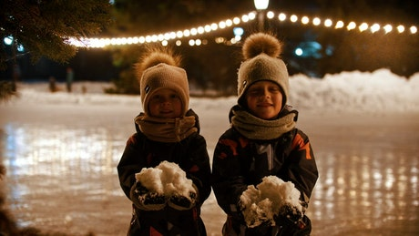 Two little kids happily throwing snow into the air