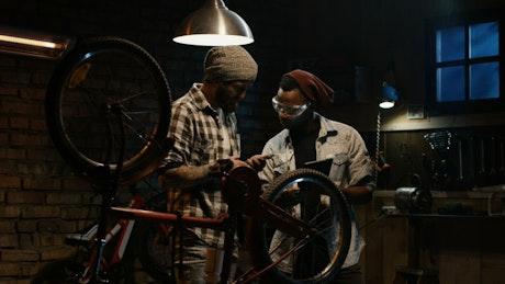 Two mechanics talking in a bike workshop