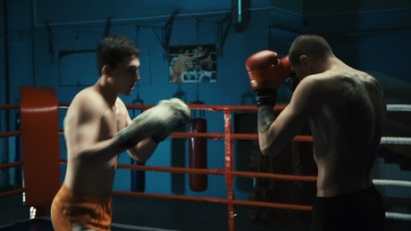 Two men are boxing on the ring