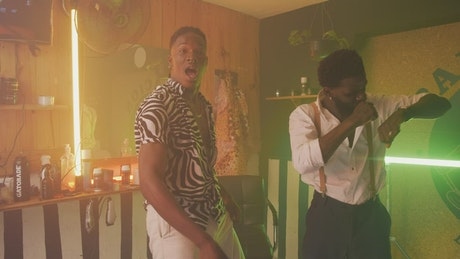 Two men dancing inside a barbershop