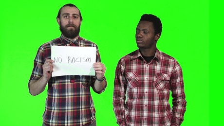 Two men holding up a No Racism sign