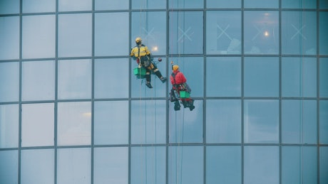Two men in red and yellow work clothes cleaning the exterior windows of a building