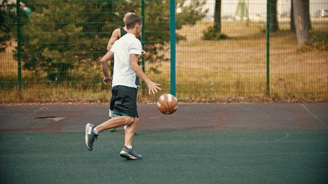 Two men playing basketball in a park