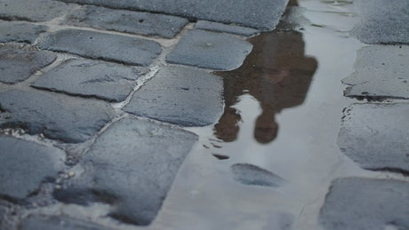 Two men reflected in a puddle
